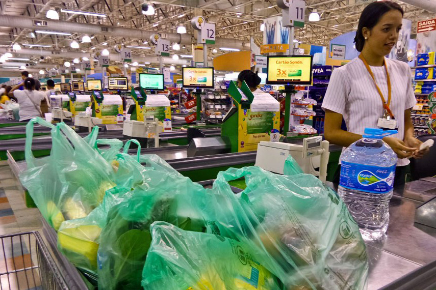 Supermercado com caixa registradora e sacolas biodegradáveis
