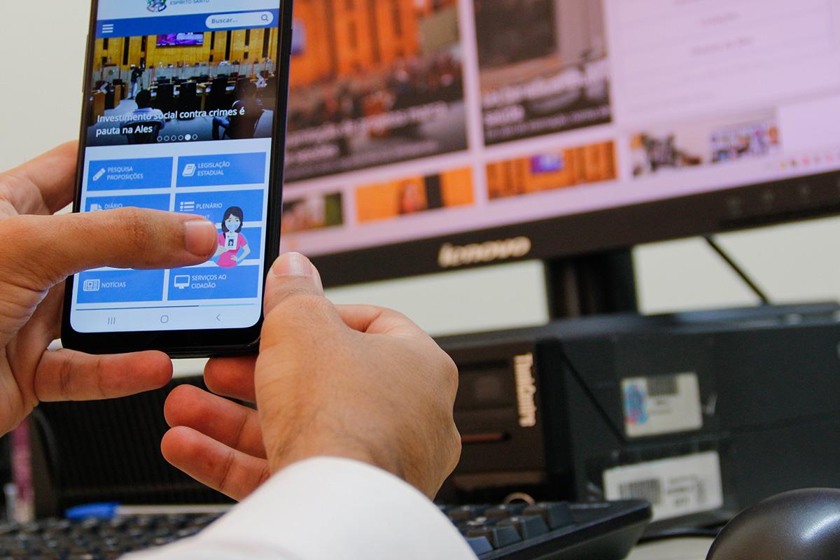 Tela de smarphone mostra ferramenta Alesinha; computador aparece ao fundo
