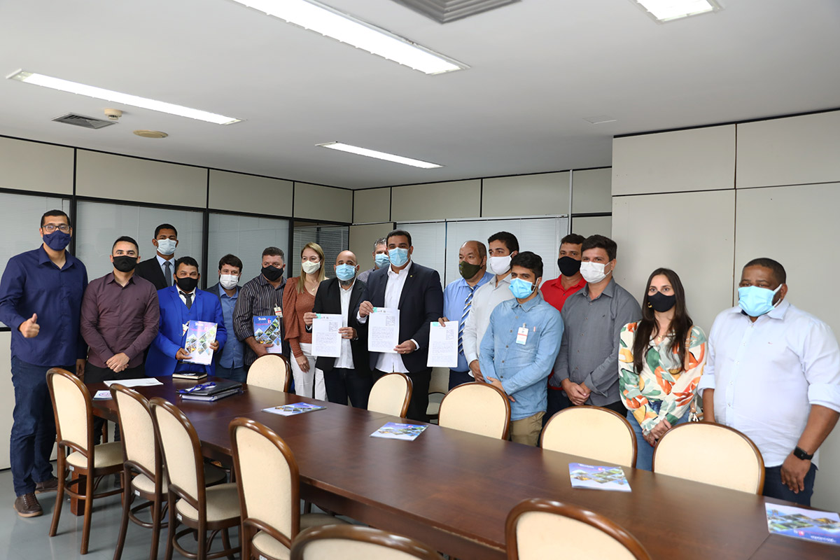 Pessoas de pé em volta de uma mesa, segurando folha de papel e de máscara